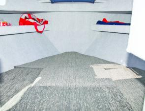 The Rebel's lined cabin features overhead shelving to complement storage below the bunks.